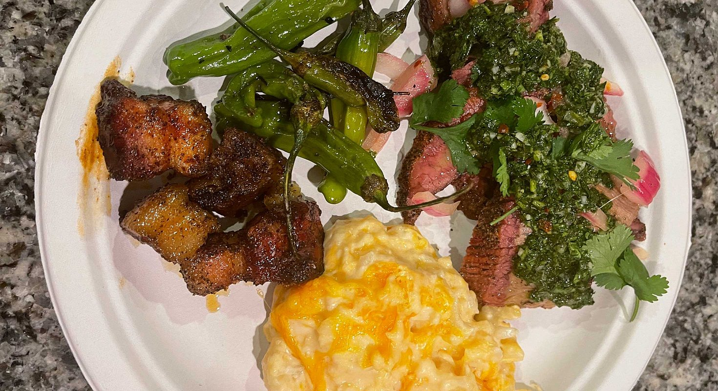 A plate of BBQ brisket, greens and  potatoes.