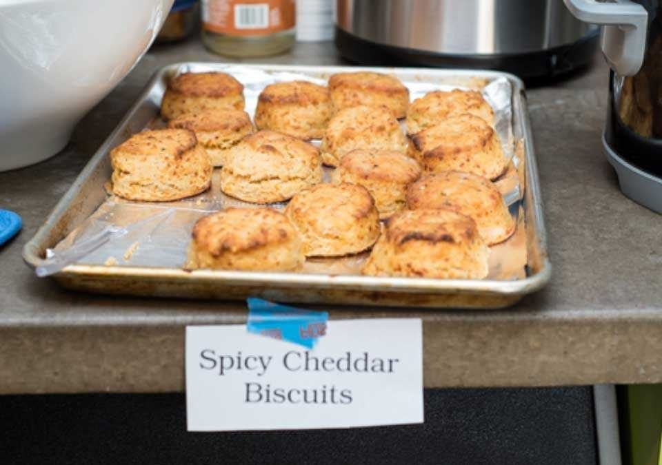 A baking pan full of fresh Spicy Cheddar Biscuits.