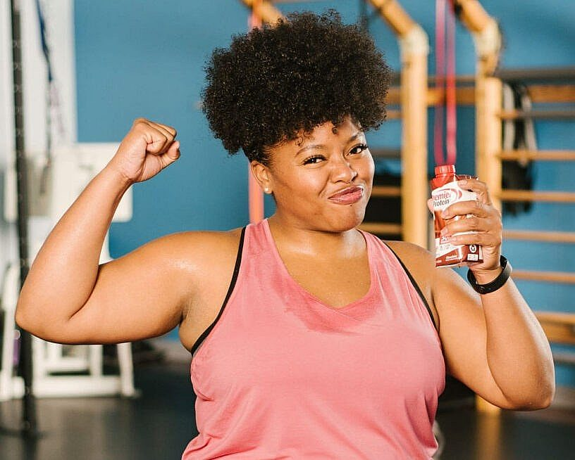 A woman in a gym flexing her muscles while drinking Premier Protein.