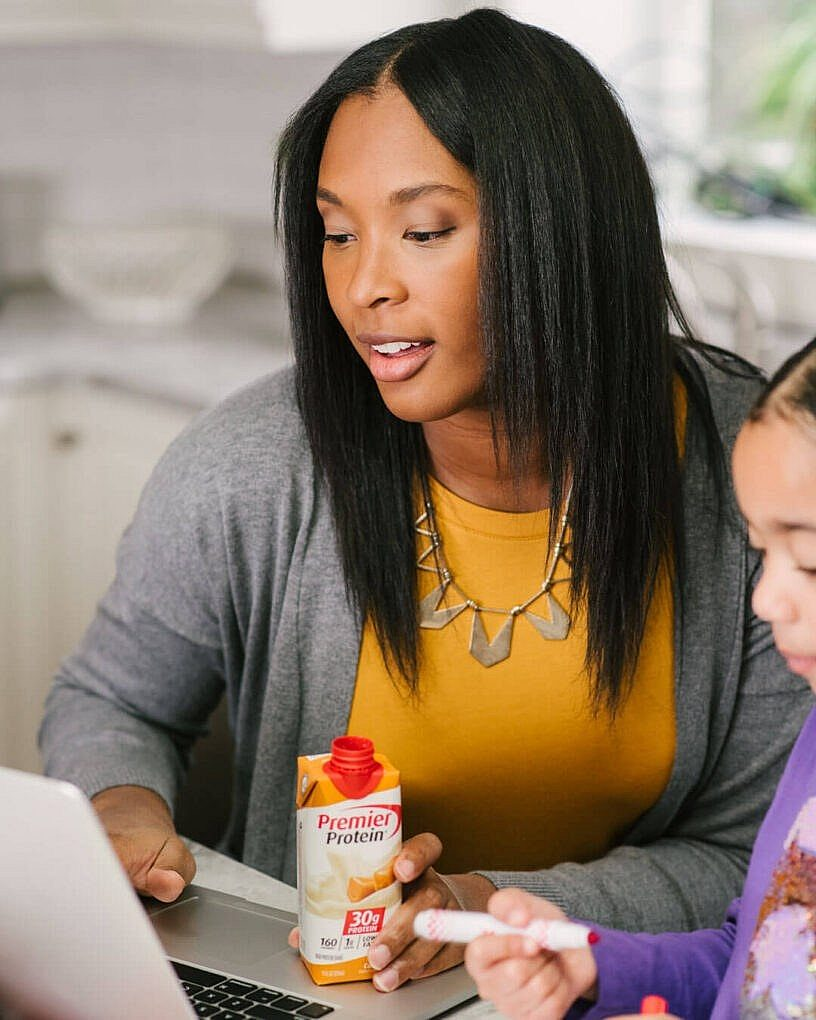 A woman in front of a computer with her daughter and drinking a Premier Protein shake.