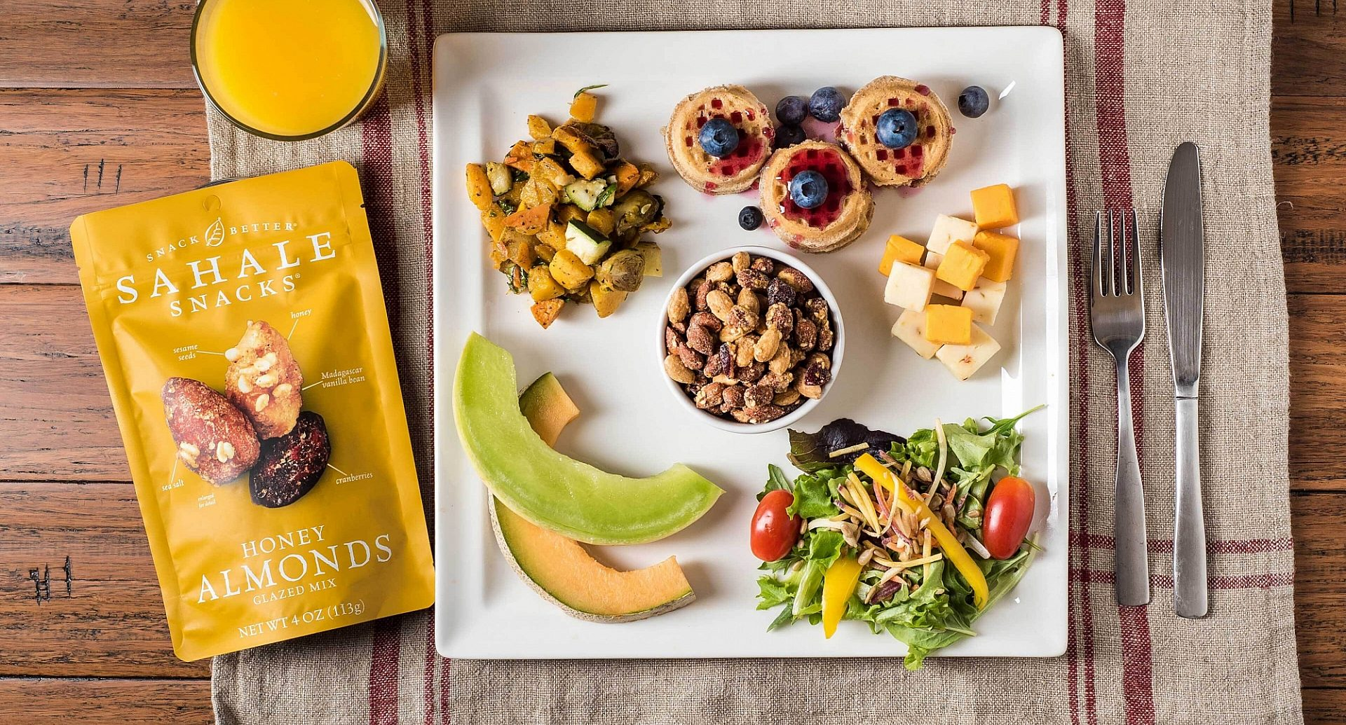 A table featuring may healthy snacks, like a back of Sahale Snacks Honey Almonds Glazed Mix
