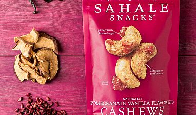 A bag of Sahale Snacks on a table next to fresh ingredients that make the product.